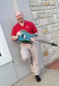 Photo of Jim Lammers with green Schecter guitar