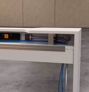 This still image from Trinity's contract furniture rendering provides visuals displaying the interior elements of the trough's electrical routing system. This is a close shot of the trough, displaying the ground power source manuevering through the interior of the trough which plugs into the extension and provides power to the individual workstations.